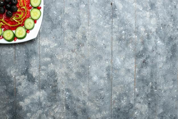 회색 소박한 책상 샐러드 야채 색상 비타민 건강 다이어트에 접시 안에 올리브와 함께 상위 뷰 슬라이스 오이