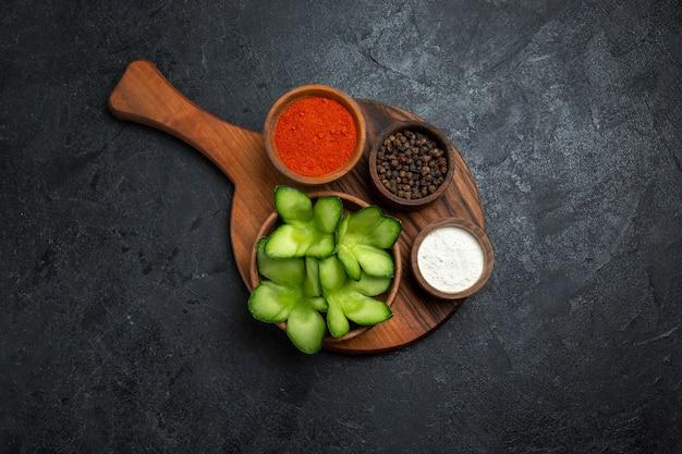 Вид сверху нарезанные огурцы с приправами на темном фоне салат здоровая овощная еда еда