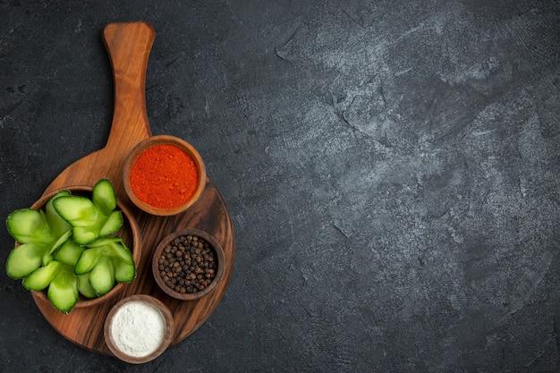 暗い背景に調味料とスライスしたキュウリの上面図サラダ健康野菜ミール食品