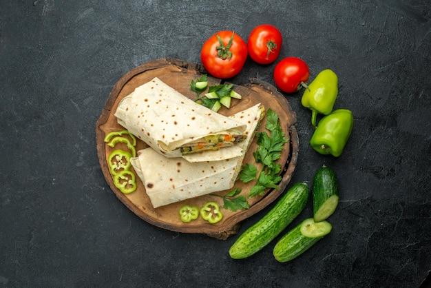 Vista dall'alto delizioso panino con insalata di shaurma affettato con verdure fresche su panino con hamburger con insalata di pita da scrivania grigia