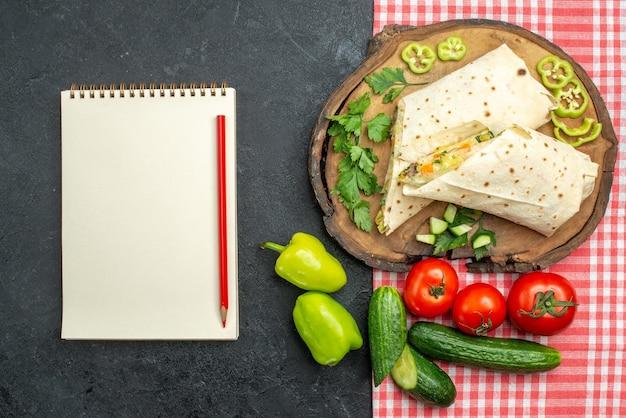 Vista dall'alto delizioso panino con insalata shaurma affettato con verdure fresche sulla superficie grigia hamburger panino con insalata pita pasto