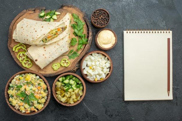 上面図スライスしたおいしいシャワルマサラダサンドイッチと野菜の灰色の表面の食事ピタサラダサンドイッチバーガー