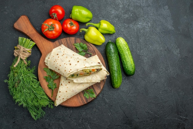 Top view sliced delicious shaurma with fresh vegetables on grey surface salad burger sandwich meal food snack