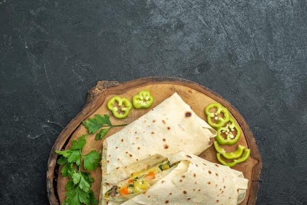 Вид сверху нарезанной вкусной шаурмы с зеленью на сером столе, салате, бургере, сэндвиче, еде
