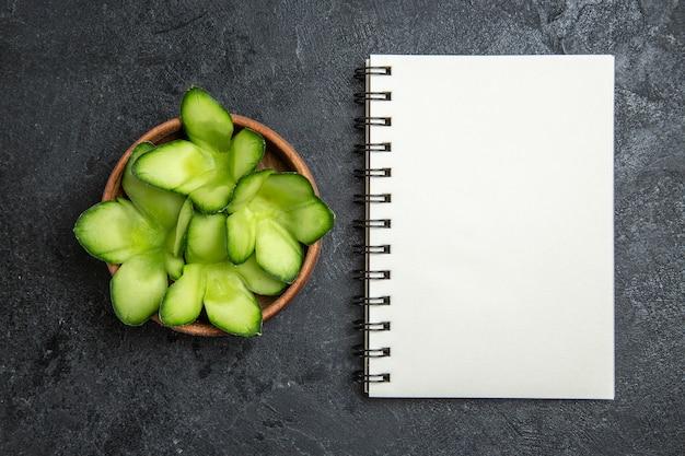 상위 뷰는 회색 배경 샐러드 건강 다이어트 야채에 냄비 안에 디자인 된 오이 슬라이스