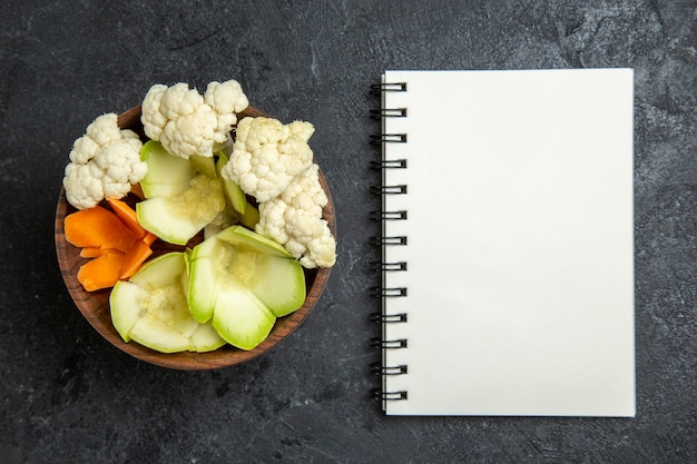 Top view sliced designed salad with notepad on grey background salad health diet vegetable
