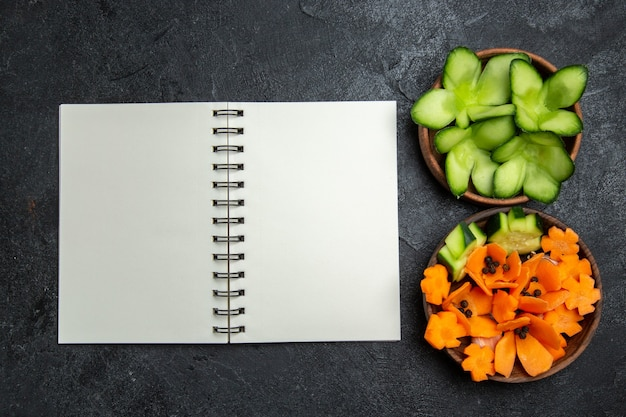 Vista dall'alto a fette di insalata progettata con blocco note su sfondo grigio insalata di salute alimentare dieta vegetale