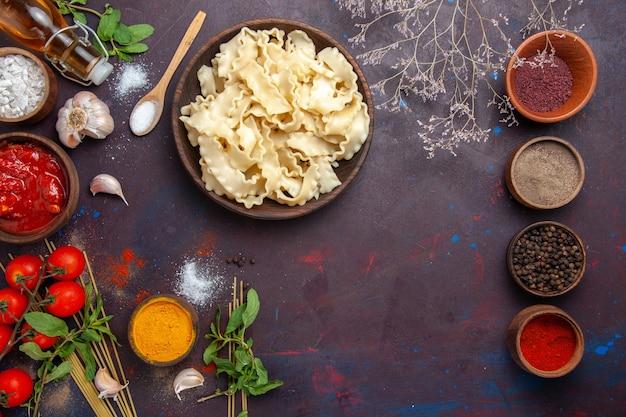 Vista dall'alto di pasta a fette con condimenti e pomodori sulla cena di pasta alimentare pasta pasto scrivania scura