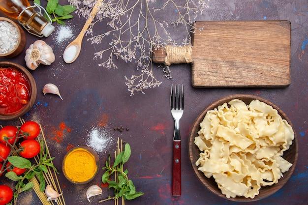 上面図スライスした生地とトマトソースと暗い背景のトマト生地食品パスタディナー