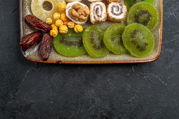 Vista dall'alto affettato frutta secca anelli di ananas e kiwi su sfondo grigio frutta secca uvetta agrodolce vitamina salute
