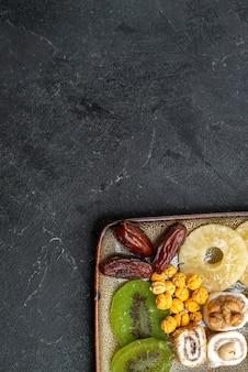Vista dall'alto affettato frutta secca anelli di ananas e kiwi su sfondo grigio frutta secca uva passa agrodolce vitamina salute