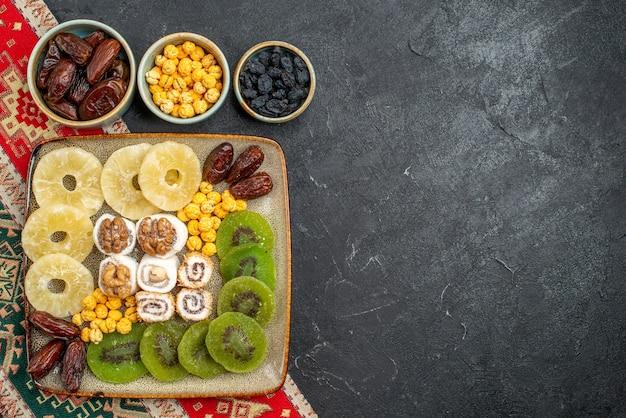 Vista dall'alto affettato frutta secca ananas anelli e kiwi su sfondo grigio frutta secca uva passa dolce vitamina acido salute