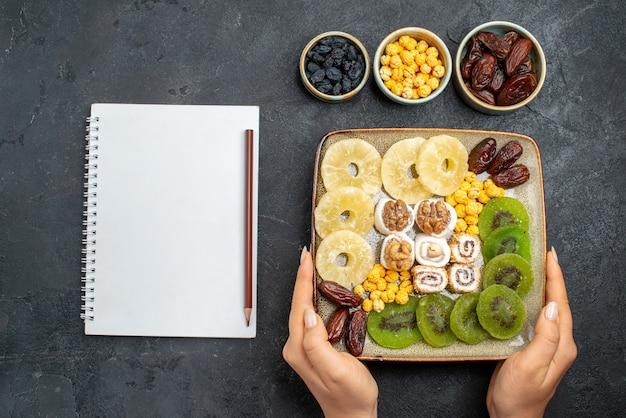 Vista dall'alto affettato frutta secca ananas anelli e kiwi sulla scrivania grigia frutta uva passa dolce vitamina acido salute