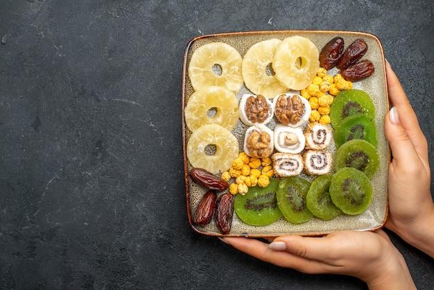 Vista dall'alto di frutta secca a fette anelli di ananas e kiwi con noci sulla scrivania grigia frutta secca uva passa dolce vitamina salute