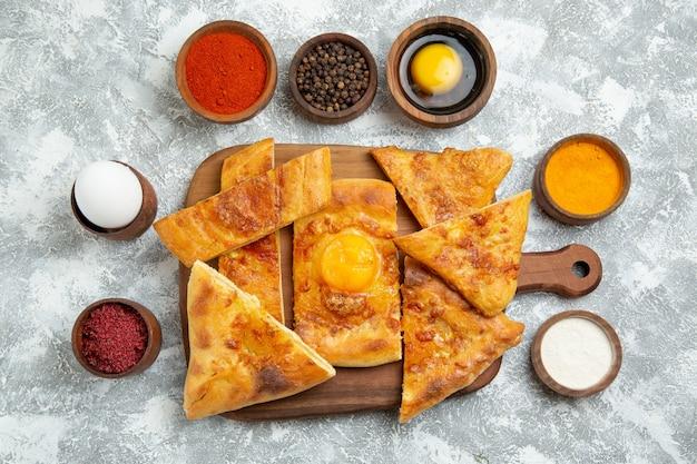 上面図スライスした卵は白い背景に調味料でおいしいペストリーを焼くペストリーは生地の食事食品ピザを焼く