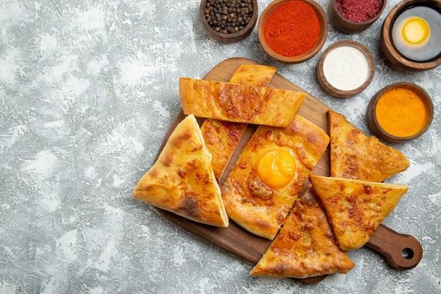 上面図スライスした卵は、明るい白の背景に調味料でおいしいペストリーを焼くペストリーは生地の食事食品ピザを焼く