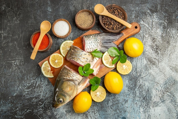 Top view sliced fresh fish with lemon and seasonings on light surface