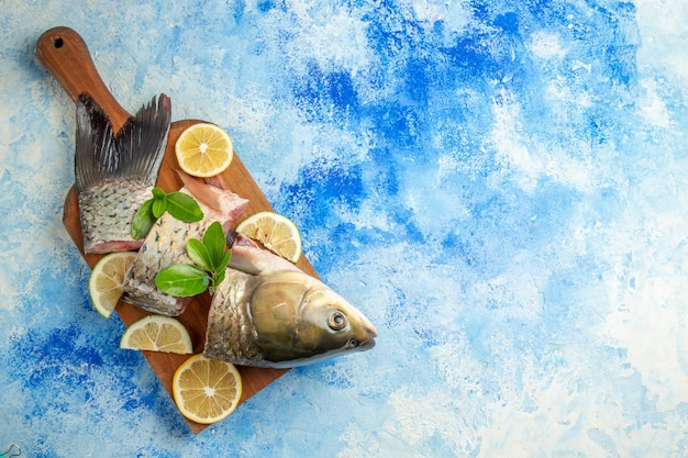 Top view sliced fresh fish with lemon slices on a blue surface