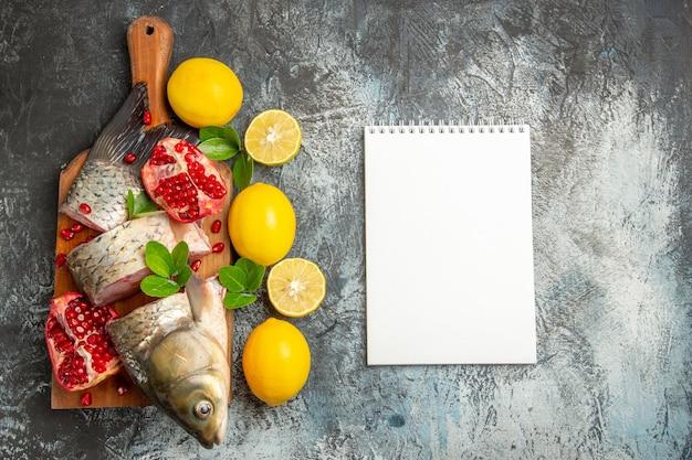 上面図ザクロとレモンを光の表面にスライスした新鮮な魚