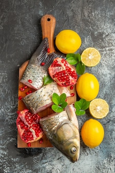 Top view sliced fresh fish with pomegranates and lemon on light surface