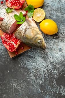 Vista dall'alto di pesce fresco a fette con melograni e limone sulla superficie chiara