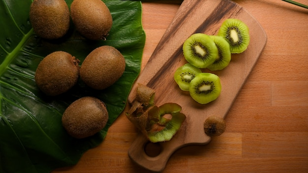 Top view of sliced fresh  kiwi fruit on cutting board and whole kiwi fruit on kitchen table