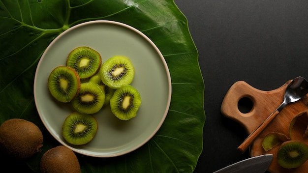 Top view of sliced fresh kiwi fruit on plate decorated with green leaf on kitchen table