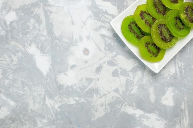 Vista dall'alto kiwi freschi affettati all'interno della piastra su sfondo bianco
