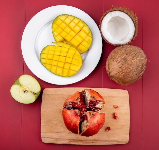 Vista dall'alto di mango fresco a fette in un piatto bianco con fette di melograno isolato su una tavola di cucina in legno con metà e intera noce di cocco e metà mela verde sulla superficie rossa