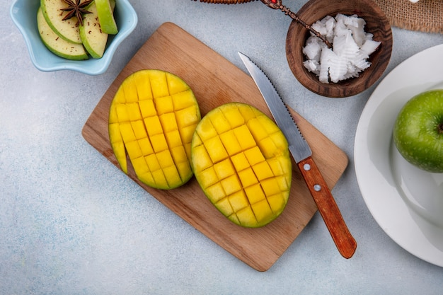 Top view of sliced fresh mango on a wooden kitchen board with knife and chopped apples in a white bowl and pulps of coconut in a wooden bowl on white surface