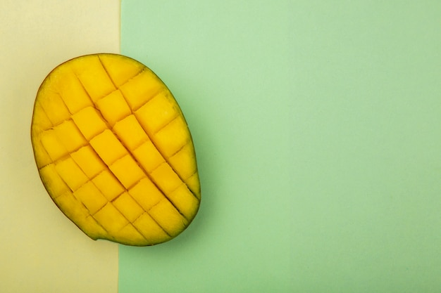 Top view of sliced fresh mango on yellow and green surface
