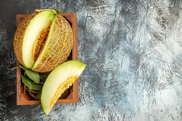Вид сверху нарезанной свежей дыни на темно-светлом столе сладкие фрукты спелое лето