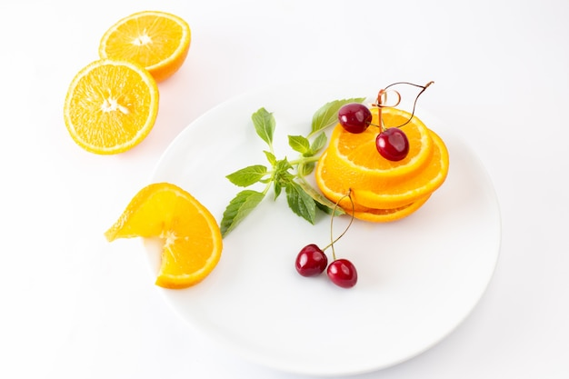 Vista dall'alto di arance fresche a fette all'interno del piatto bianco insieme a ciliegie rosse su sfondo bianco succo di frutta esotica