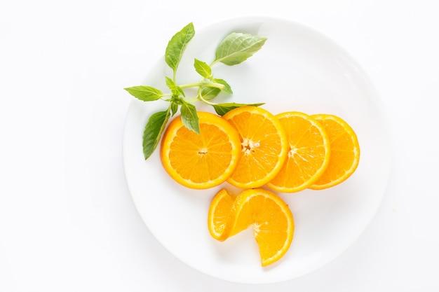 Вид сверху нарезанных свежих апельсинов внутри белой тарелки на белом фоне сока экзотических фруктов