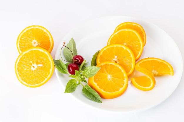 Vista dall'alto di arance fresche a fette all'interno del piatto bianco sul succo di colore della frutta sfondo bianco