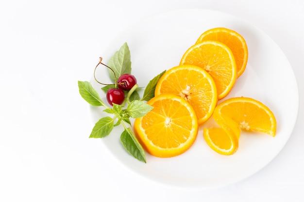 Vista dall'alto di arance fresche a fette all'interno del piatto bianco sul succo di colore della frutta esotica scrivania bianca