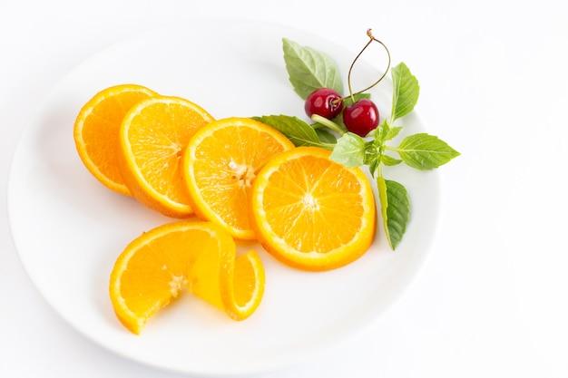 Vista dall'alto di arance fresche a fette all'interno del piatto bianco con coppia di ciliegie su sfondo bianco frutta esotica colore succo