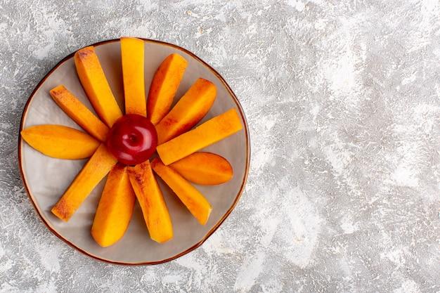 Vista dall'alto di pesche fresche a fette all'interno del piatto su superficie bianca chiara