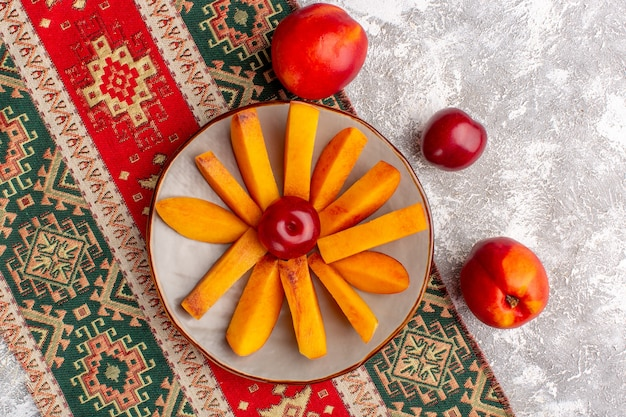 Top view of sliced fresh peaches inside plate on light-white surface