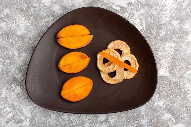 Vista dall'alto di pesche fresche a fette all'interno del piatto con anelli di ananas sulla superficie bianca chiara