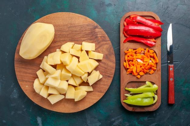 Вид сверху нарезанный свежий картофель, очищенные овощи на темно-синем фоне