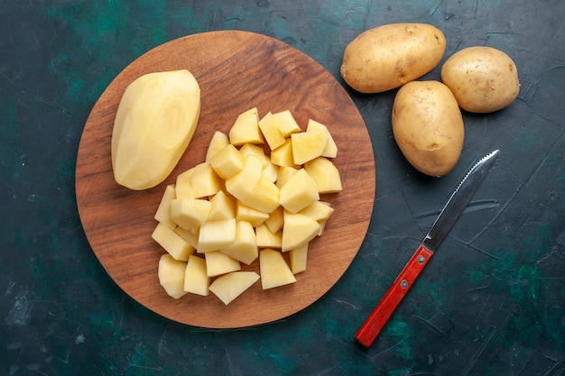 Top view sliced fresh potatoes vegetables on dark-blue background