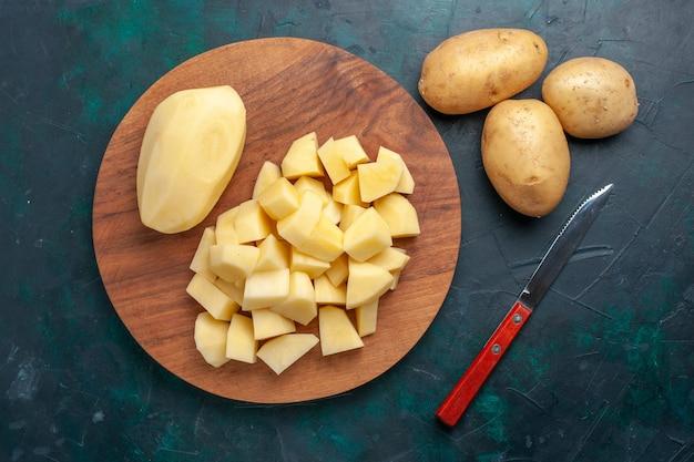 Vista dall'alto patate fresche a fette verdure su sfondo blu scuro