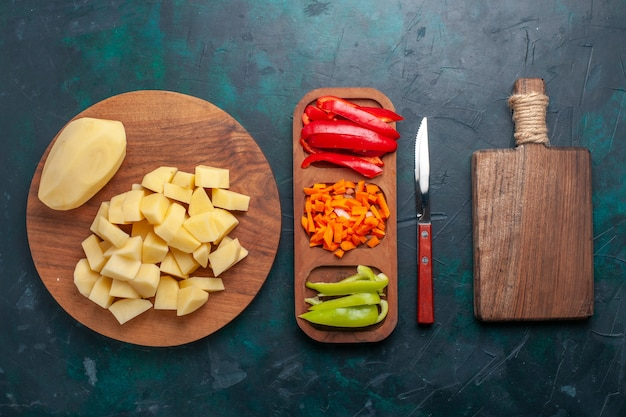 Vista dall'alto di patate fresche a fette con peperoni a fette su sfondo blu scuro