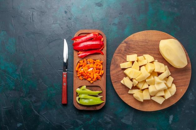 상위 뷰는 진한 파란색 배경에 얇게 썬 고추와 신선한 감자를 썰어