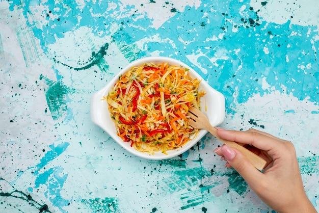 上面図スライスした新鮮なサラダ野菜サラダプレート内の女性が明るい青色の机の上に保持食品食事野菜サラダスナック
