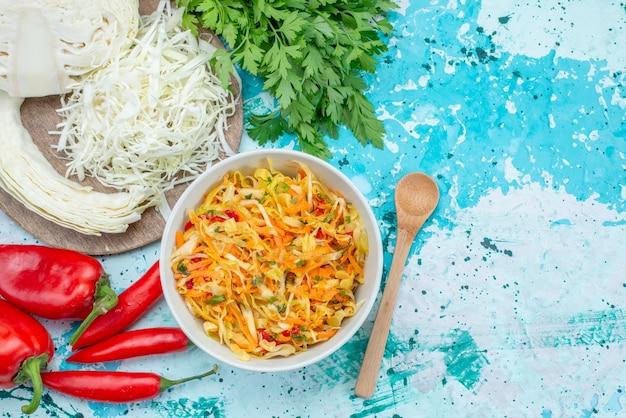 상위 뷰는 밝은 파란색 바닥 음식 식사 야채 샐러드에 녹색 양배추 고추와 함께 접시 안에 신선한 야채 길고 얇은 조각 샐러드를 슬라이스