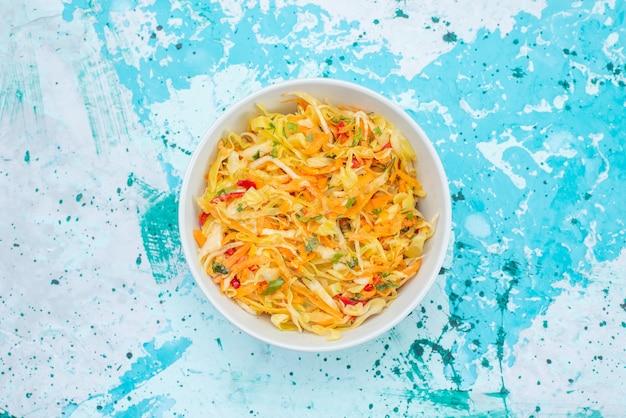 上面図スライスした新鮮な野菜の青の背景の丸いプレートの内側の長くて薄いピースサラダ