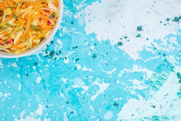 上面図スライスした新鮮な野菜の長くて薄いピースのサラダ、明るい青色の背景の丸いプレートの内側の食品食事野菜サラダ
