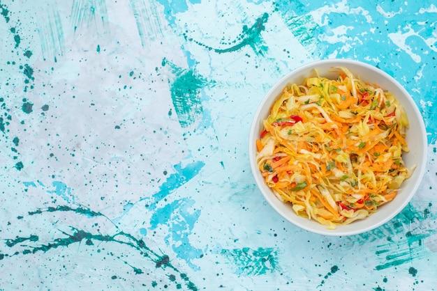 Vista dall'alto di verdure fresche affettate insalata di pezzi lungo e sottile all'interno della piastra sullo sfondo blu insalata di verdure pasto alimentare